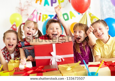Group of adorable kids looking at camera with giftboxes near by #133673507