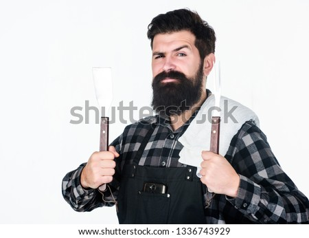 Best barbecue cookware. Bearded man holding barbecue tools in hands. Grill cook using spatula and barbecue fork. Happy hipster holding stainless steel tools for preparing barbecue food. #1336743929