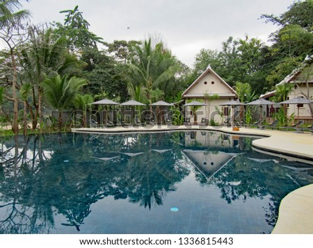 Curved swimming pool surrounded by sun umbrellas and cabins. Nobody is using the pool and reflections are perfect. #1336815443
