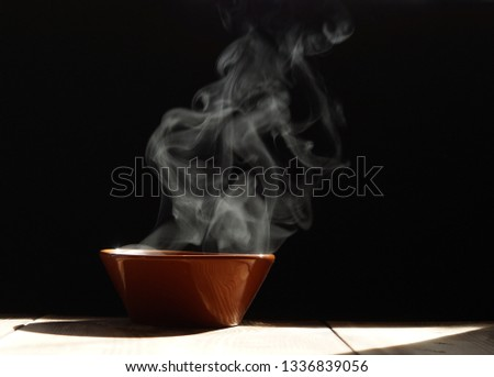 bowl of hot soup with steaming on wooden table on black background Royalty-Free Stock Photo #1336839056