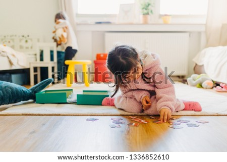 little girl with brown hair collects a puzzle on the floor in the nursery, another blond girl plays in background #1336852610