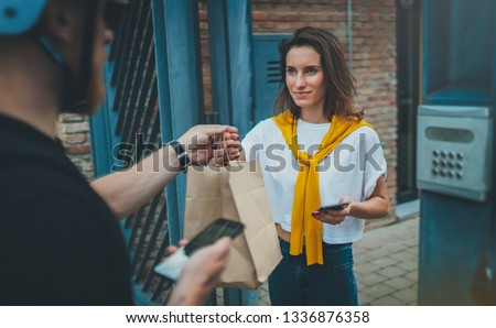 Male courier with bicycle delivered no name shopping bag to the client.Courier delivery food service at home #1336876358