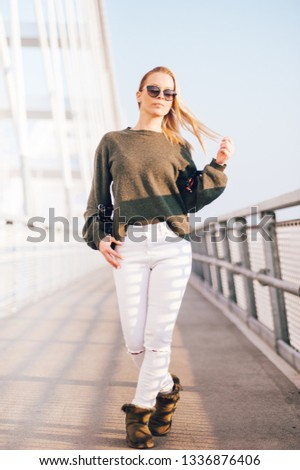 Young and pretty blonde girl posing on the long bridge. Nice sunny day. Young and fashionable girl concept. #1336876406