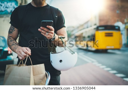 Tattooed Man courier using a map app on mobile phone to find the delivery address in the city.Courier bicycle delivery food service at home #1336905044