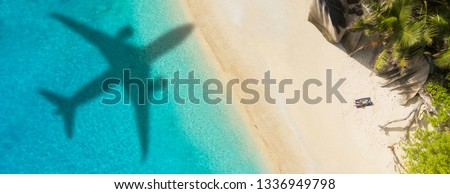 Concept of airplane travel to exotic destination with shadow of commercial airplane flying above beautiful tropical beach. Beach holidays and travel. #1336949798
