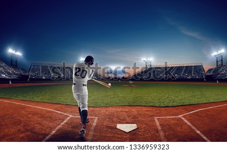 Baseball player at professional baseball stadium in evening during a game. #1336959323