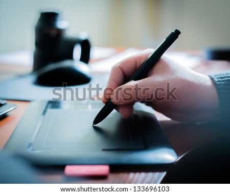 Graphic designer using digital tablet and computer in the office