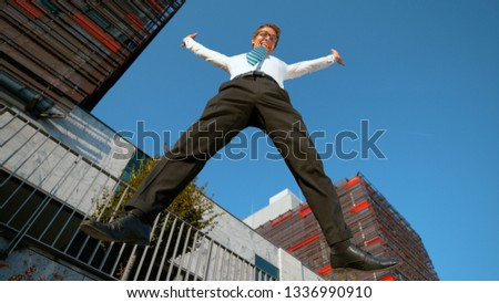 LOW ANGLE: Cheerful young businessman jumps and outstretches his arms after a productive day at work. Carefree Caucasian man jumping high in the air as he celebrates finishing important work project. #1336990910