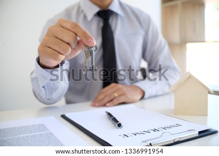 Sales manager giving advice application form document, considering mortgage loan offer for car and house insurance #1336991954