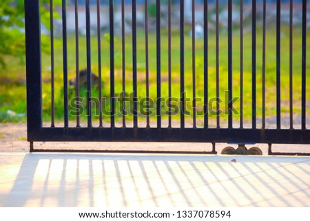 A gate of a house in the morning,fence iron, metal fence,shadows of metal fence,Metal black gate  #1337078594