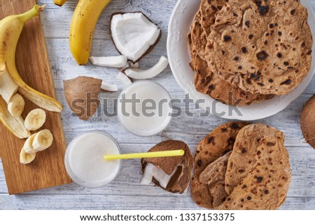 Close up on whole wheat asian flatbread roti with lactose free coconut milk and ripe banana on a cutting board, top view, flat lay, horizontal #1337153375