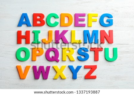 Plastic magnetic letters on wooden background, top view. Alphabetical order