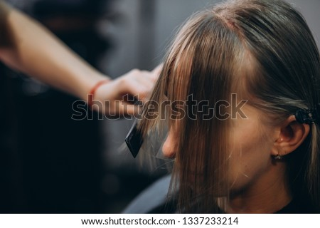 Hairdresser cuts hair by scissors beautiful blonde girl #1337233214
