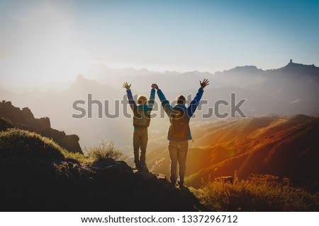 Father and son travel in sunset mountains, family hiking in nature #1337296712