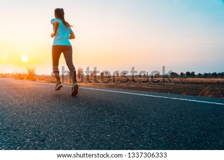Young asian woman enjoys running outside with beautiful summer evening in the countryside. #1337306333