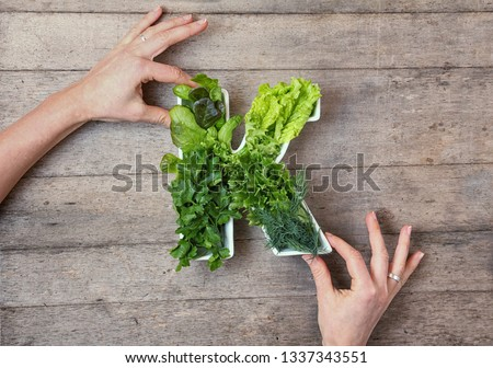 Vitamin K in food concept. Woman's hands holding plate in the shape of the letter K with different fresh leafy green vegetables, herbs,  lettuce on wooden background. Flat lay or top view. #1337343551