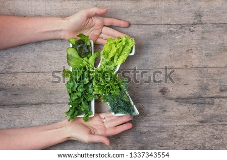 Vitamin K nutrient in food concept. Woman's hands holding letter K shaped plate with different fresh leafy green vegetables, herbs, lettuce on wooden background. Flat lay or top view. #1337343554