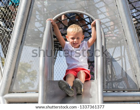 Little boy riding down the metal slide on the playground #1337361377