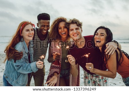 Multiracial friends enjoying at beach with sparklers. Group of young men and women having fun with fireworks at the sea shore. #1337396249