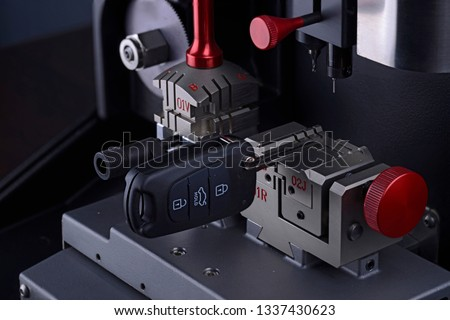 Close view of key copying machine with key. Duplicate machine make new key. Locksmith theme. Blank keys for cutting. Black modern car door opener. #1337430623