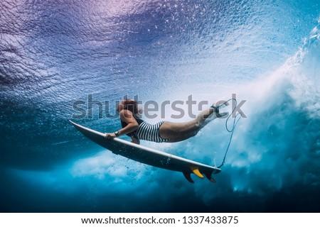 Surfer dive underwater. Surfgirl dive under big wave #1337433875