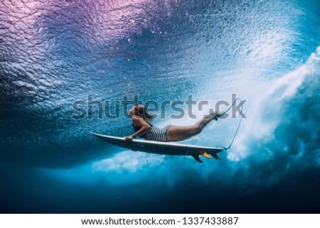 Surfer dive underwater. Surfgirl dive under big wave #1337433887