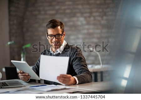 Happy male entrepreneur having a busy day at work while reading business reports and using digital tablet.  #1337445704