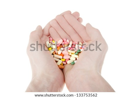 Color pills in hands isolated on white background #133753562