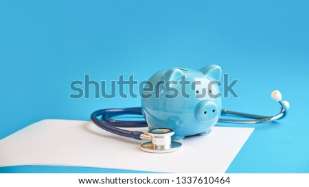 Piggy bank with stethoscope isolated on blue background. tax offset concept. Medical Expense Deductions and Tax Breaks #1337610464