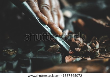 Closeup hands of craftsman carve with a carve tools in the hands.Traditional craftsman carving wood.Thailand Royalty-Free Stock Photo #1337645072