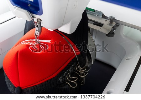 Working white embroidery machine embroidering logo on red and black sport cap, close up picture #1337704226