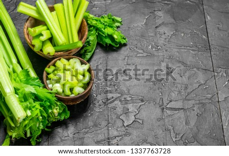 Pieces of celery in a wooden bowl. On rustic background #1337763728