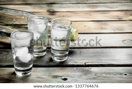 Vodka in a bottle and glasses with ice. On wooden background #1337764676