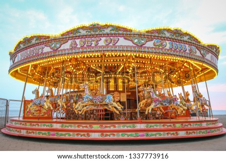 Carousel with warm lights during a summer evening near the sea Royalty-Free Stock Photo #1337773916