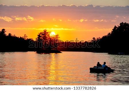 A beautiful Muskoka sunset is enjoyed by two people aboard a paddleboat. #1337782826