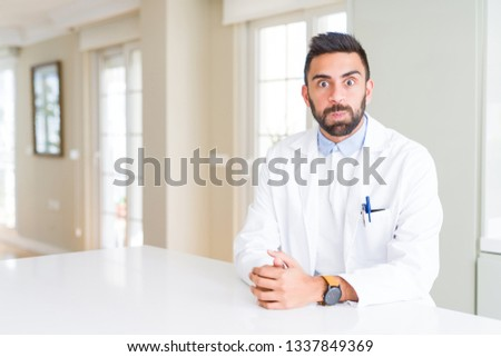 Handsome hispanic doctor or therapist man wearing medical coat at the clinic puffing cheeks with funny face. Mouth inflated with air, crazy expression. #1337849369