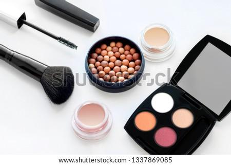 Set of decorative cosmetics on white background. Ball blush, cream eye shadow, palette of shadows, mascara, blush brush #1337869085