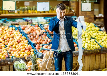 Portrait of an elegant man with shocked emotions holding very long shopping list while buying food in the supermarket #1337883041