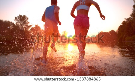 CLOSE UP, LENS FLARE: Unrecognizable active woman and man running towards the spectacular sunset and splashing river water. Carefree sporty couple jogging in the serene summer nature at golden hour. #1337884865
