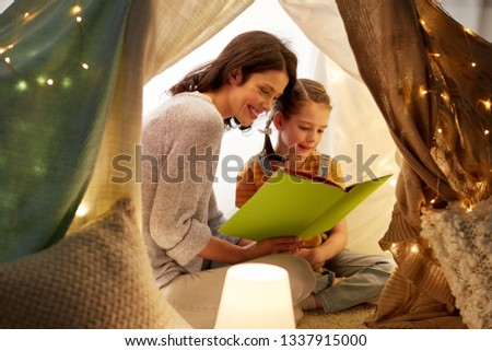 family, hygge and people concept - happy mother and little daughter reading book in kids tent at night at home #1337915000