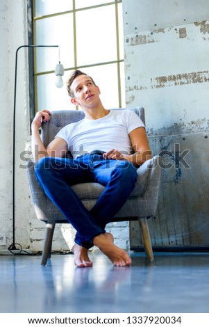 A young handsome man relaxing in a armchair in a loft style apartment #1337920034