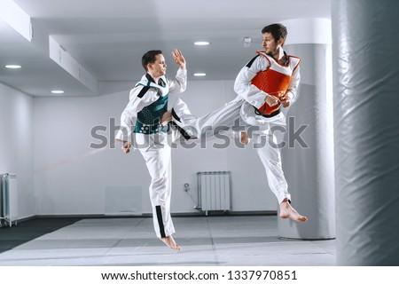 Two Caucasian sporty men sparring in tekwondo fittings barefoot. #1337970851