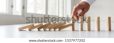 Hand of a business crisis manager stopping falling dominos to prevent a total collapse and establish stability. #1337977202