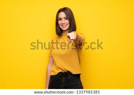 Young woman over yellow wall points finger at you with a confident expression Royalty-Free Stock Photo #1337981381