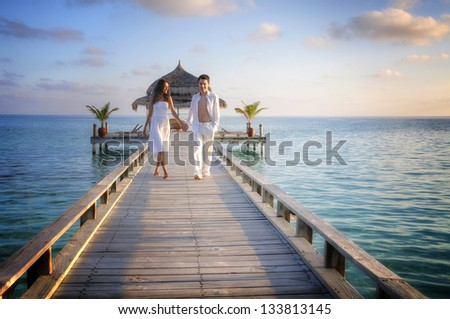 Happy loving couple in white clothes walking on a pier on Maldives #133813145