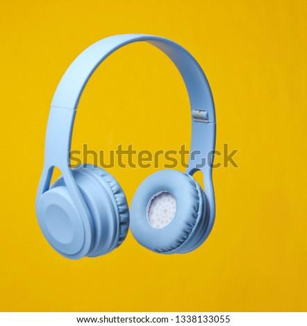 3D surround photo blue wireless headphones on yellow background.