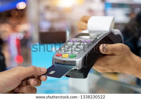 Cropped view of womens hand using credit card to make contactless payment on chip and pin machine #1338230522