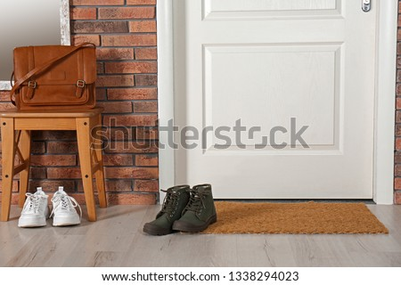 Hallway interior with shoes, bag and mat near door #1338294023