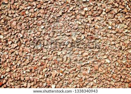 The surface is made of small reddish reddish bright gravel for the background, wallpaper, design. #1338340943