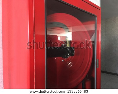 Fire hose reel in red cabinets rack on the gray cement wall.  #1338365483